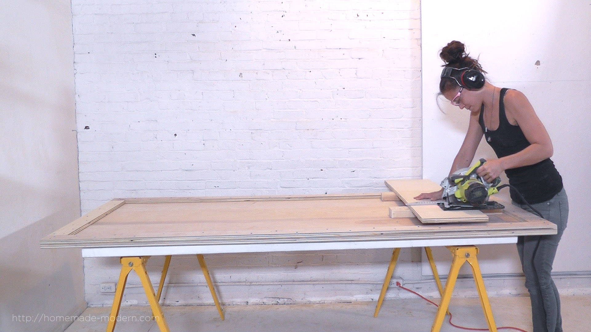 "This DIY Modern Bed is made from a sheet of ¾"" plywood, and 10 ikea shelf brackets. The materials cost  less than $100 and only 3 power tools are needed to build it. Full instructions can be found at HomeMade-Modern.com."