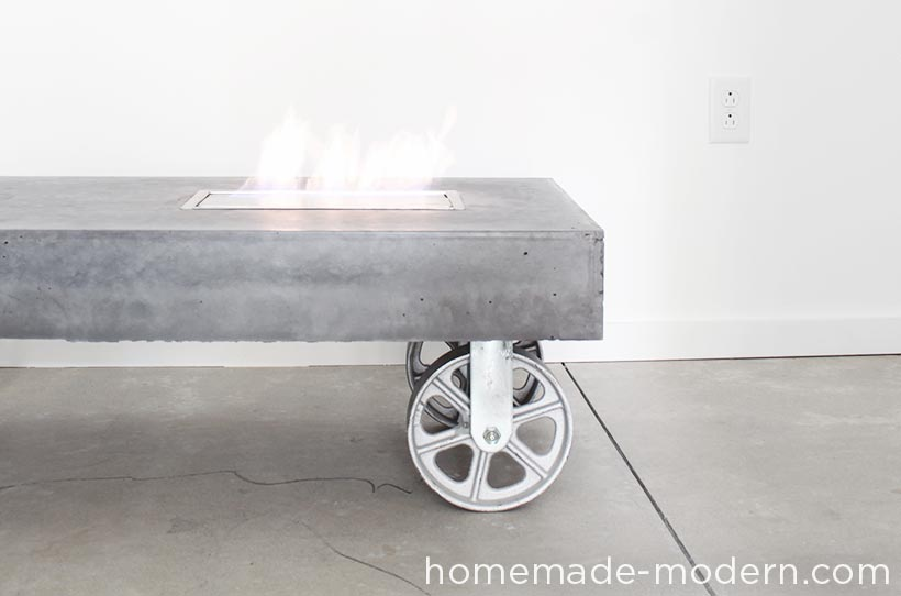 This modern concrete fireplace doubles as a coffee table on wheels. I used Quikrete 5000 cement mix poured into a melamine mold to make the table and added charcoal pigment from Quikrete to give the concrete a dark grey color. The manufacturer of the fireplace insert claims that bio-ethanol fuel is safe indoors and out, but I would only use the table outdoors. I was curious about ethanol fireplaces so I bought one from Moda Flame (not a sponsor) and made a simple, concrete table on wheels out of Quikrete 5000 that has an opening to accommodate an ethanol fireplace burner. For more information go to HomeMade-Modern.com.